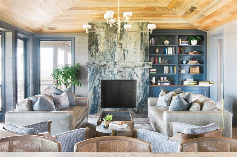 "With the Tide: Situated on the top floor, the main living space is dominated by a fireplace set in ""Blue Tides"" granite from AGM Imports. Horsehair grasscloth wallpaper in ""Clydesdale"" by Phillip Jeffries continues the textural feel evoked by the stone's veining. Leather sofas from Verellen and Osborne & Little fabric-clad club chairs by Holly Hunt lend warmth and comfort to the scene, illuminated by Cartwright New York's hand-brushed brass ""Otto Luce"" chandelier."