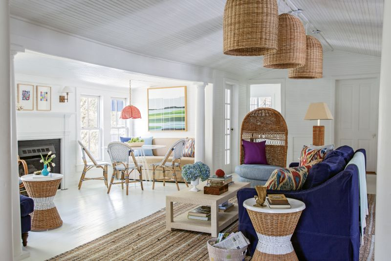 Big Imagination: For the living area, Isbell created three spaces in the former dining room. Serena and Lily wicker pendants and a slip-covered sofa delineate the main seating area, capped by a vintage hooded wicker chair from Chairish. A banquette from Ballard and bistro chairs from Serena and Lily comprise the breakfast nook.