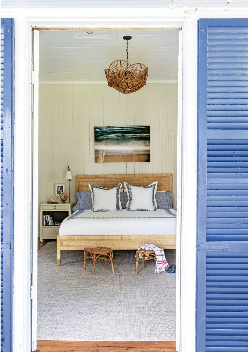 Comfortable Quarters: A large Dash and Albert rug softens the master bedroom, which has its own access to the porch. Two vintage rattan stools provide the perfect spot to drop the towels post-beach day, and a pair of Bungalow 5 bedside tables are the ideal place to stash summer reading.