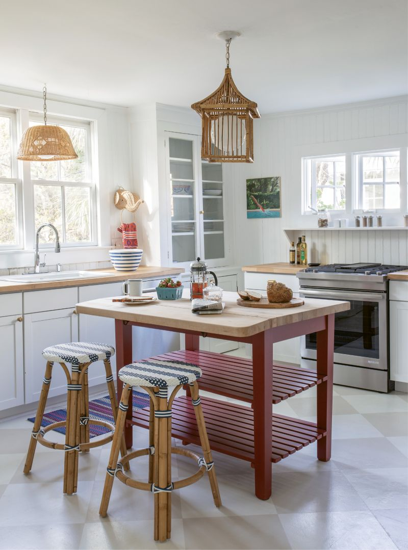 Gather 'Round: Working around the original glass-fronted cabinets in the kitchen, Isbell added a butcher-block island to allow for flexible seating in the space. On the floor, a chessboard pattern painted by Suzanne Allen Studio continues the theme of painted wood flooring seen throughout the home.