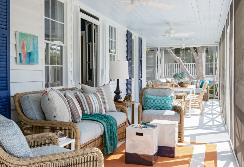 Designed for the Elements: The large porch runs the length of the home, providing a dining space for 10 as well as an outdoor living area, furnished with seating from Lane Venture and pillows from Candelabra.