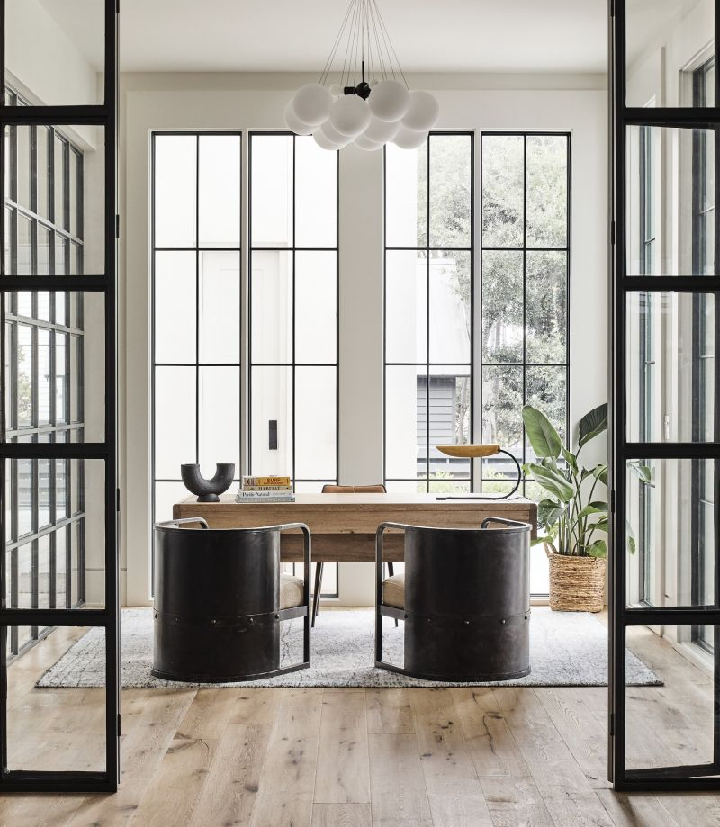 Iron barrel-back chairs and a bulbous chandelier provide balance in the rectilinear iron and glass home office, where a washed walnut desk from Noir adds warmth.