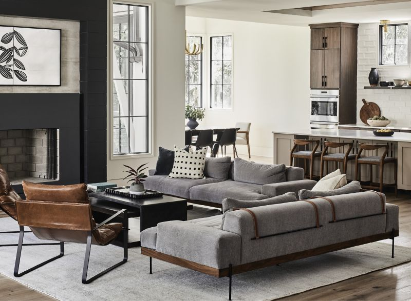 Anchored by a steel-wrapped fireplace surround with large-format tile above the mantel, the living space features low-profile iron and walnut sofas upholstered with a family-friendly performance fabric. A large wool rug helps define the space.