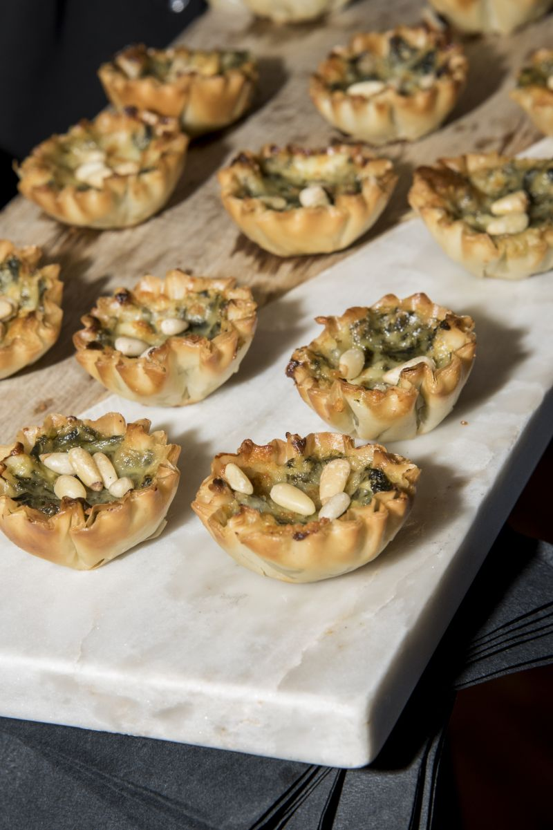 Guests snacked on hors d'oeuvres such as spinach tarts with goat cheese and almonds before sitting down for dinner.