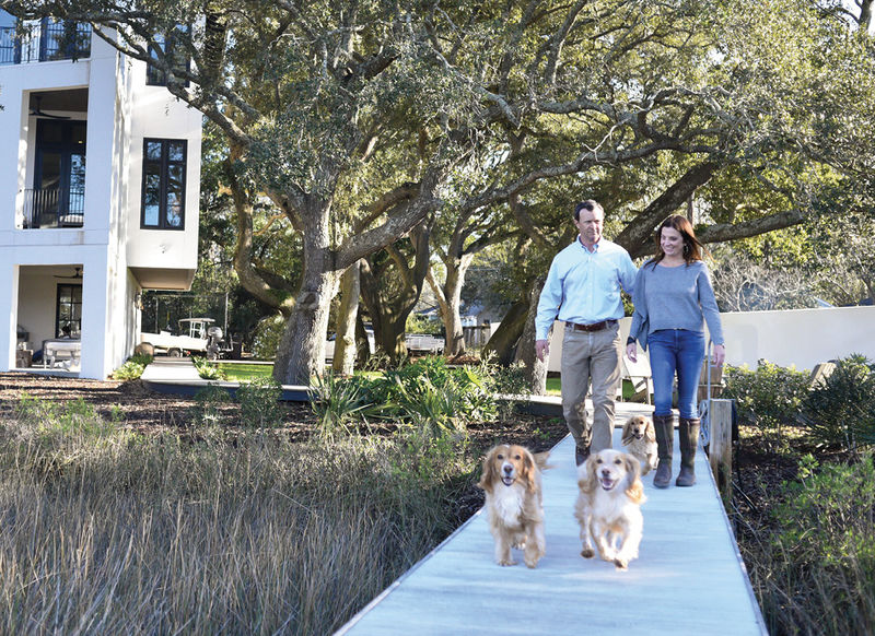 Owners Alix and Mark Bragg pictured with their three pups, Kay, Peanut, and Junior) tackled this conundrum by taking a cue from the trees and building upward. The finished project marries a bold modern design with a soft Mediterranean warmth in a special Lowcountry setting.