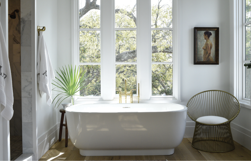 "BATHING BEAUTY: It may look sleek and minimal, but this Laura Kirar freestanding bathtub from Kallista weighs more than 500 pounds. Installing it into Alix's personal oasis ""required a few good men,"" she says. Brass fixtures from Moluf's, a chair from Celadon Home, and a painting from Antiques of South Windermere pop in the all-white space."