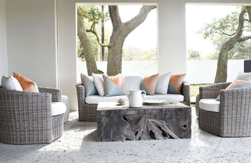 Grey wicker furniture from Celadon Home anchors the outdoor lounging space, with a pop of color provided by Serena and Lily pillows; the spectacular Artesia coffee table from GDC Home pays homage to its deep-rooted neighbors