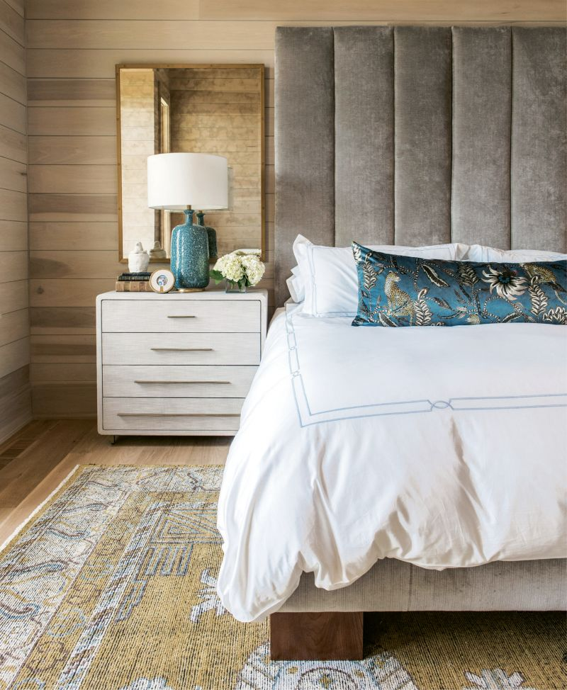 In the couple's bedroom, poplar-clad walls, velvet lumbar pillow (fabric from Ardmore Design), velvet headboard (custom designed by Erickson and upholstered by Powell's Upholstery), and antiqued glass mirrors layer on the luxe.