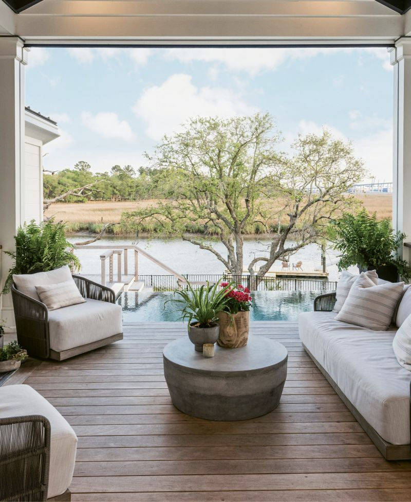 The comfortably appointed covered back porch overlooks the pool and Ralston Creek.