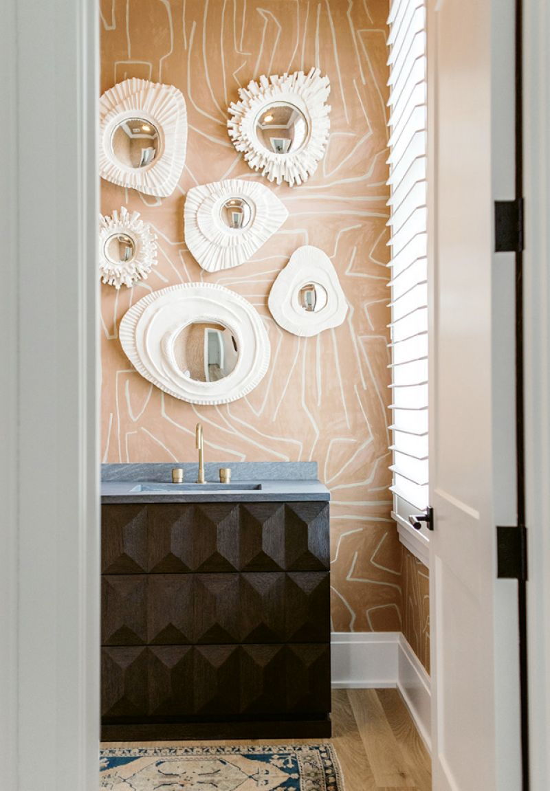 With its graphic wallpaper and plaster mirrors, the powder room packs a punch.