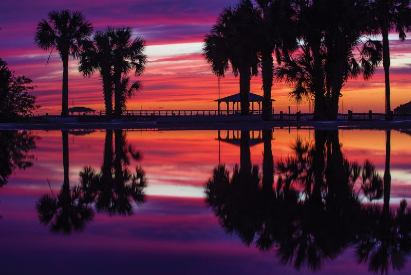 An epic April sunset over Folly River Boat Ramp reflects in the empty parking lot puddled with rainwater.