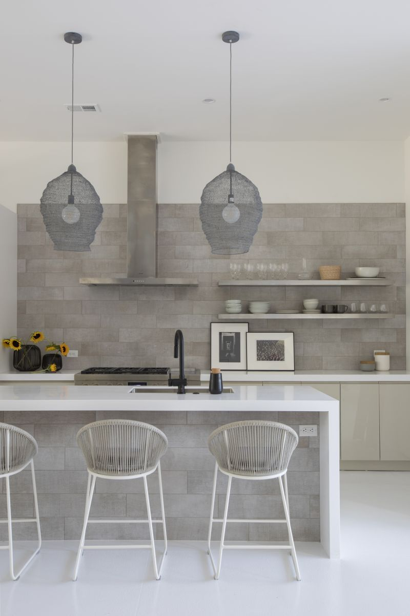 The tile—ceramic with a burlap feel on the wall and island—offers a textural backdrop for the high gloss cabinetry and matte Corian countertops.