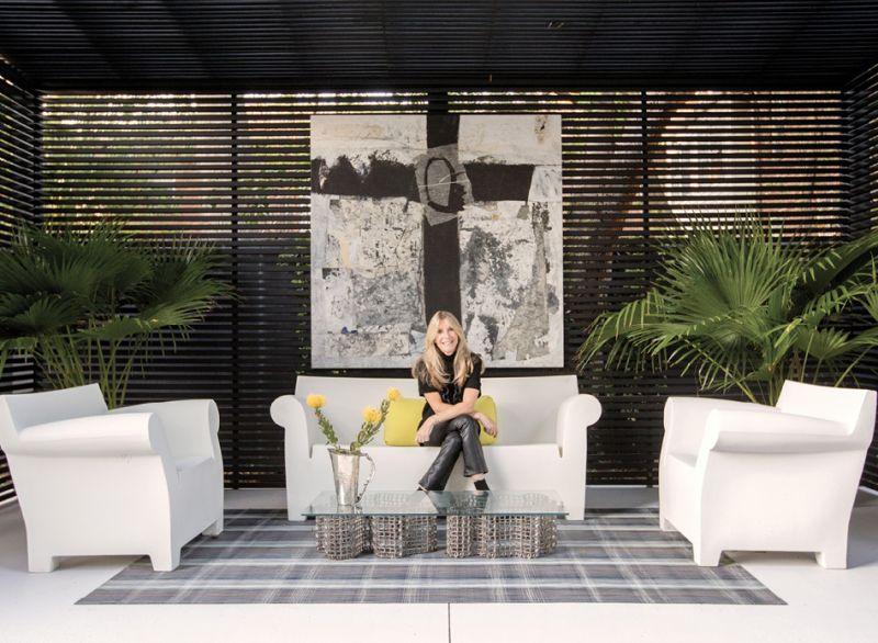 Homeowner Karen Baldwin (pictured in the backyard cabana with artwork by Michael Brangoccio) is an avid supporter of Charleston's contemporary art scene.