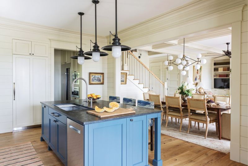 """COUNTER CULTURE: A soapstone-topped island, painted in """"Silent Night"""" from PPG, ties the living-dining room into the spacious kitchen. Just beyond the glass doors is the outdoor kitchen and dining room, where Martha and Paul enjoy entertaining friends and family."""
