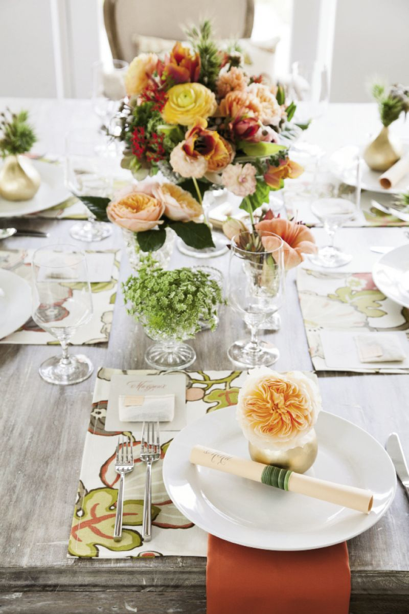 GARDEN PARTY: Flanking the dominant arrangement and topping place settings with bud vases added pops of color throughout.