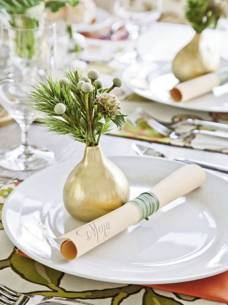 BUDDIES: Menus were printed in-house on peach-toned paper with a calligraphy-style font, then wrapped and tied with long-stemmed grass. Topping place settings with bud vases added pops of color throughout.