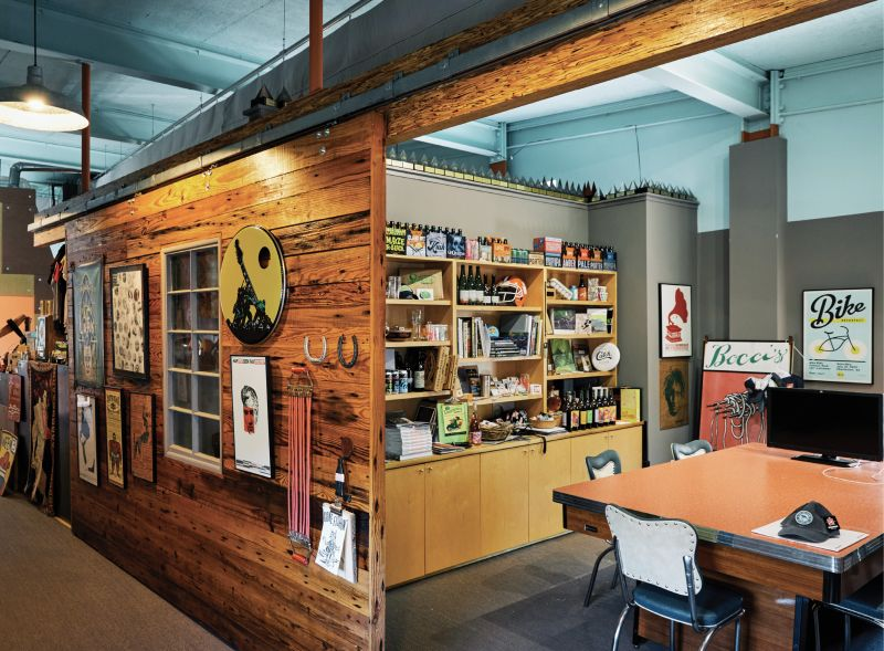 Products emblazoned with Shuler's designs— from beer cans and wine bottles to books, brochures, posters, and more—fill the shelves in the conference room.