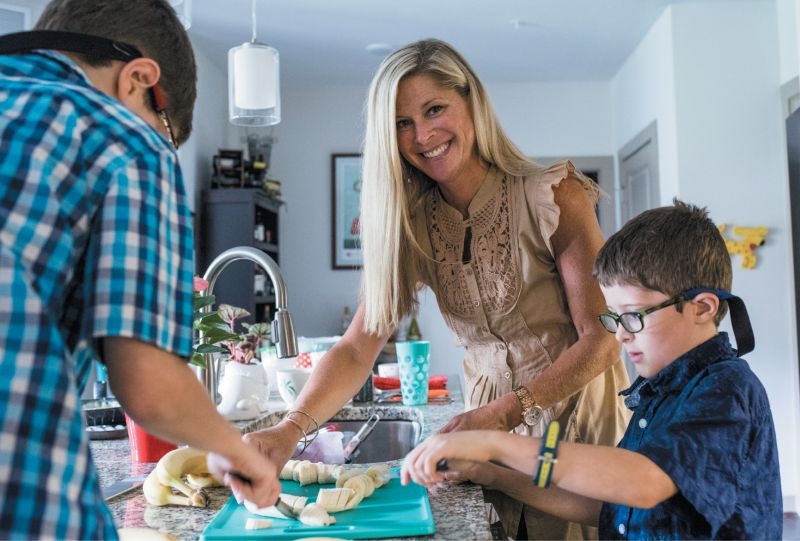 Angel Postell and sons Riley (left) and Chase (right) make dinnertime fun by prepping locally grown produce together, slicing bananas for pudding and Brussels sprouts and tomatoes for pasta salad.