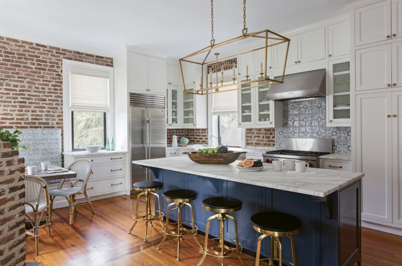 In the second-floor kitchen, Peake played off the navy blue of the island with complementary patterns in the tile backsplash and the washed linen fabric for the banquette.