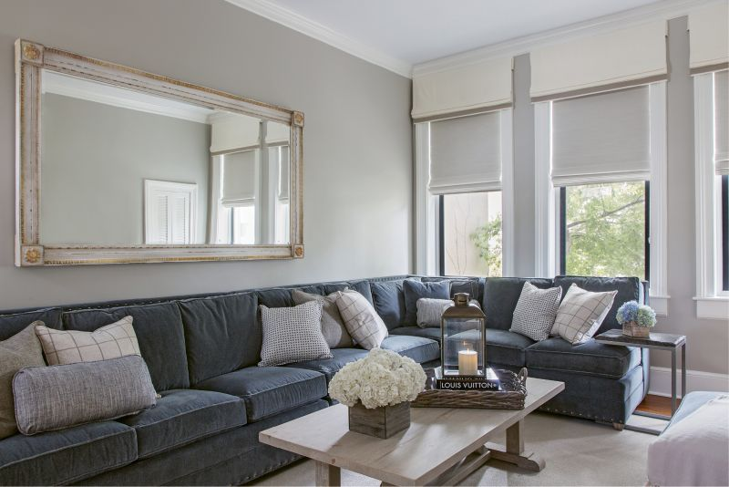 "Rick's only request for the décor? ""He said he wanted a really comfortable couch,"" says Kristy. The custom sectional from Vanguard offers plenty of seating in the family room. Instead of elaborate window treatments that could easily overtake the decor, Peake chose light-hued, space-saving woven shades and had the window mullions painted in ""Kendall Charcoal"" by Benjamin Moore for a modern look that highlights the woodwork while creating depth."