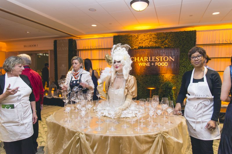 Svetlana Pavlova offers wine glasses to guests as they arrive.