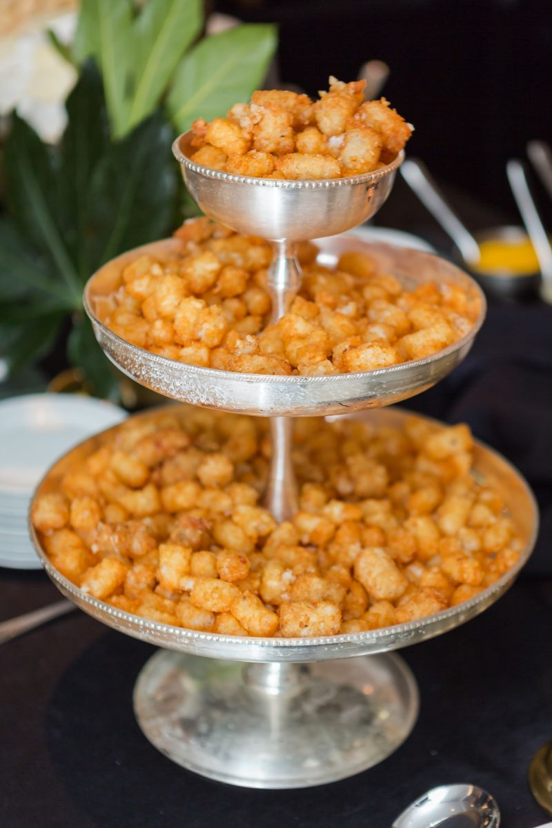 Three-tiers of tater tots on a silver pedestal, ready to be served with caviar.