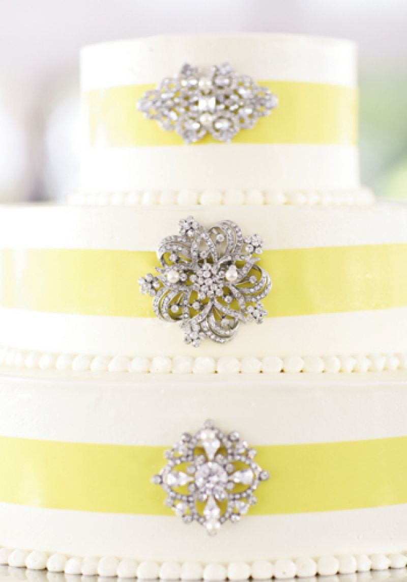 SPARKLY SWEET: With its ribbon and vintage broaches, the three-tiered cake by Fish Restaurant played off the soft yellow of the bride's bouquet and the ornate crystal detail of her belted gown.