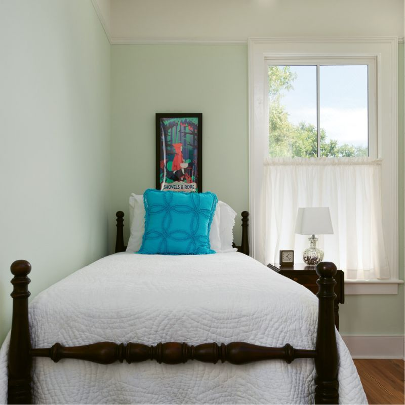 In this petite guest room, a vintage twin bed with a carved pineapple motif and a Shovels & Rope poster add local flavor.