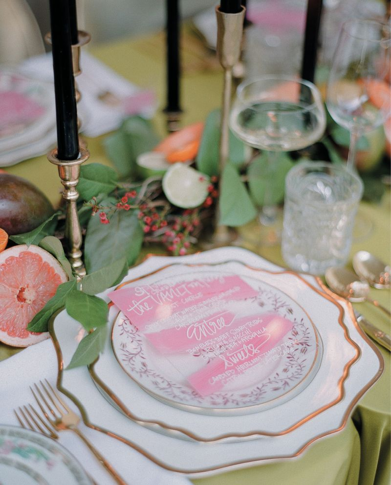 Each place setting of classic white and gold china chargers and dinner plates was topped with a uniquely patterned salad plate, as well as hand-painted acrylic menu cards by Mary Ruth Miller.
