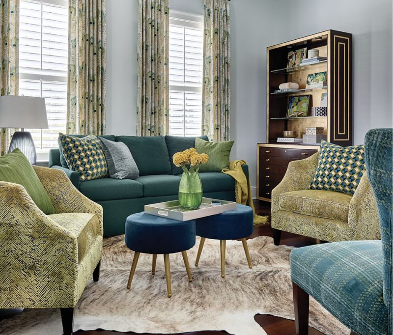 """Two Baker """"Butterfield Barrel Chairs"""" covered in a citrus-green fabric provide the focal point for the striking home office. Peacock feather drapes, a cowhide rug, and two velvet footstools complete the luxe look."""