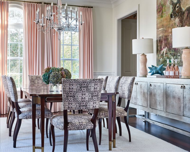 In the dining room, pastel pink drapes from Greenhouse Fabrics continue the light, feminine feel, bringing playful hues to the more formal space.