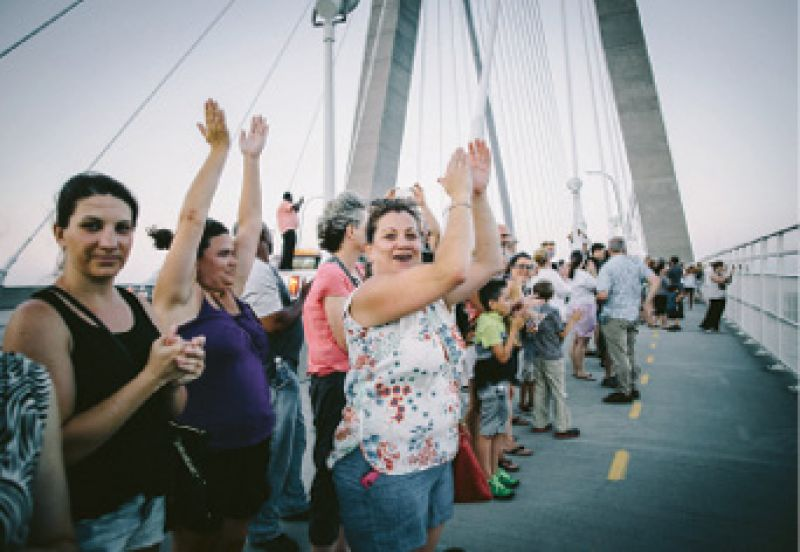 "An estimated 15,000 people joined hands in a ""Bridge to Peace"" unity chain across the Ravenel. Though uplifting and symbolic, it was ""an immediate emotional response, not real change,"" says Rev. Dr. Kylon Middleton. Photograph by Floyd Smalls Jr."