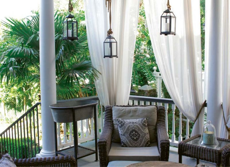 """Scenic Overlook: Shaded by palm trees and sheer white curtains, the back porch is outfitted for year-round living with a whirring ceiling fan, a quartet of comfy wicker chairs, and a galvanized tub for icing drinks. """"We're out here constantly,"""" says Susan."""